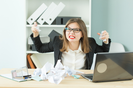 People, business and emotions concept - Angry woman sitting at desk in office throwing around scraps of paper