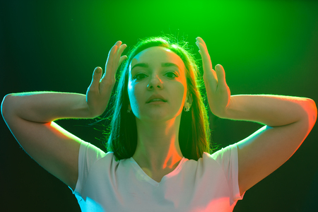 Dance, jazz funk, sport and people concept - young woman dancing in darkness and holds her hands near her face Stock Photo