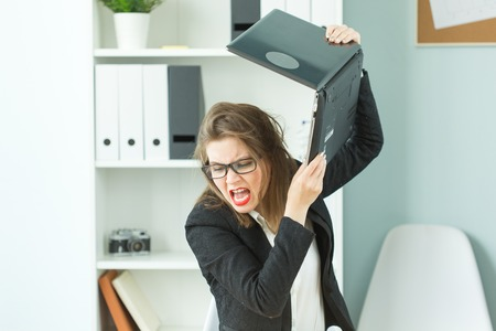 Stress, office and people concept - stressed angry business woman breaking up her computer Banque d'images