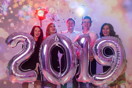 New 2019 Year is coming. Group of cheerful young people holding silver colored numbers and throwing confetti on the party. Stock Photo