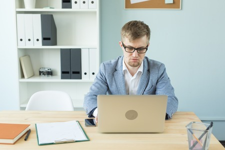 Business, technologies and people concept - Handsome man working in office on laptop