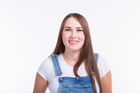 Portrait of a smiling pretty woman in denim overall isolated on white background 版權商用圖片