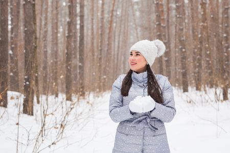 Christmas, holidays and season concept - Young beautiful smiling woman holding snow in hands in winter outdoors Stock Photo