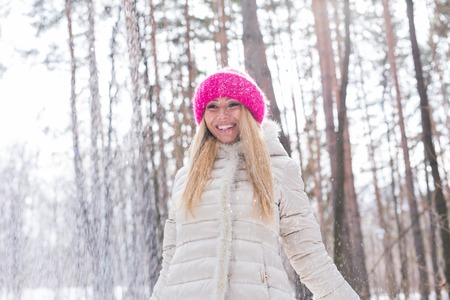 Happy young woman plays with a snow at snowy forest outdoor Archivio Fotografico