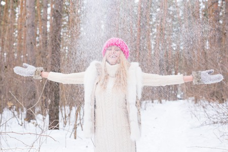 Season, leisure and people concept - young woman is happy and throwing snow in the winter nature Stock fotó