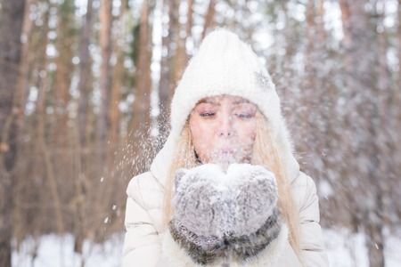 Christmas, holidays and season concept - Young happy blond woman blowing snow in the winter nature Stock fotó