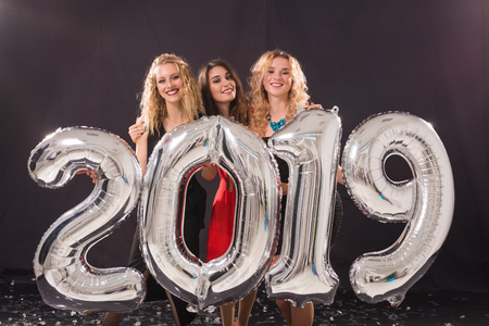 New Year party concept. Group of young women holding silver colored numbers 2019 and throwing confetti