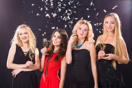 Party, holidays, celebration and nightlife concept - smiling female friends with glasses of champagne in club