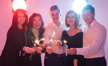 Celebrating with fun. Group of cheerful young men and women carrying sparklers. New year, holidays and party concept.