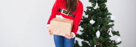 Christmas, xmas, new year and happiness concept - Close up of woman in santa helper hat with gift box near Christmas tree background with copy space