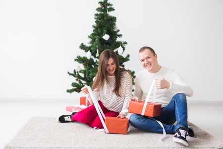 Happy young couple celebrating at home. Handsome man and woman opens gift boxes Banco de Imagens