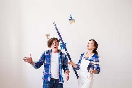 Renovation, redecoration and people concept - Funny handsome man and attractive woman with instruments over white wall background