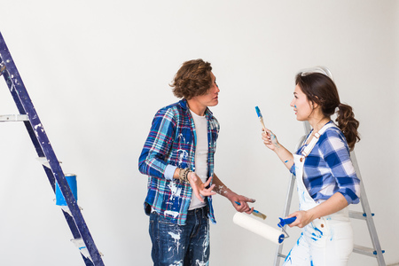People, renovation and repair concept - Young woman and man discussing new apartment