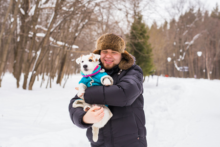 Pet owner, dog, and people concept - Young smiling caucasian man holding Jack Russell terrier outdoor in winter time.
