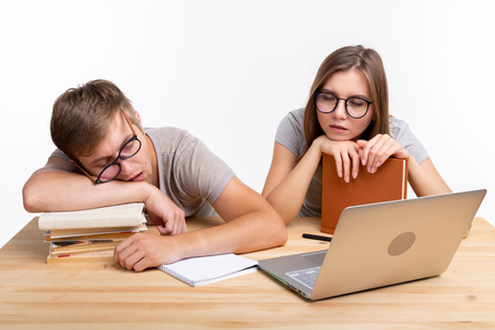 Education, people concept - a couple of young people in glasses look like they are bored of learning homework