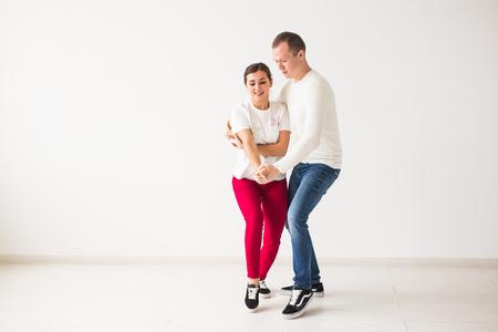Happy couple dancing social dance kizomba vs bachata or salsa or zouk on light background