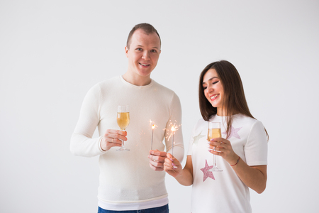 Valentines Day concept - Young happy smiling cheerful attractive couple celebrating with glasses of champagne and sparklers on white background