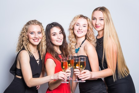 Party, new year and people concept - Cheerful young women with glasses of champagne at the party