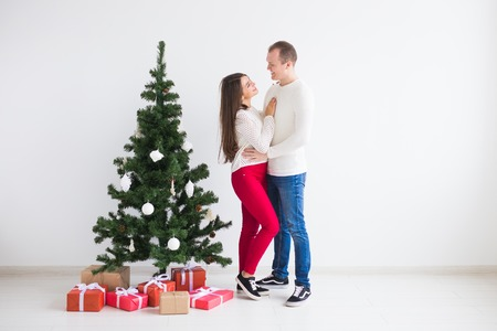 People, christmas, holidays and new year concept - happy love couple in sweaters standing near christmas tree