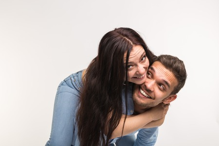 Fun and relationship concept - Man carrying girlfriend on his back on white background