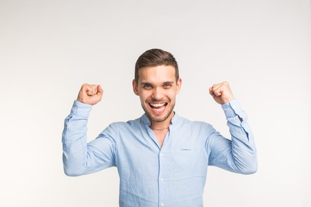 Emotions, victory and people concept - Handsome joyful man with his arms up over white background Stock Photo