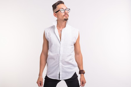 People, clothing and style concept - young sexy handsome man posing in white shirt on white background