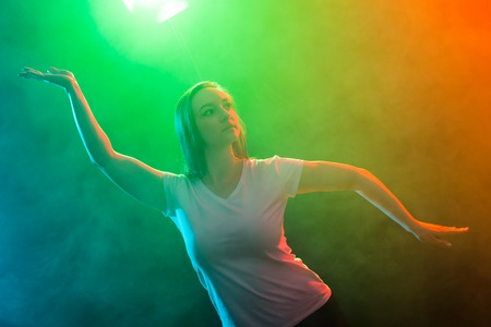 Young beautiful slim woman dancing jazz-funk on colourful background