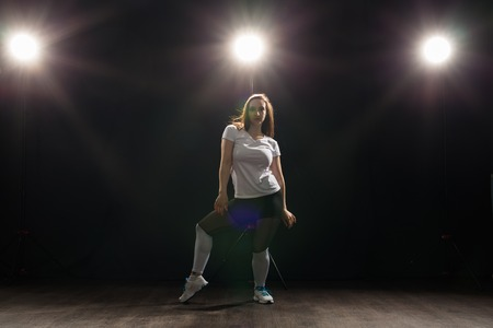 Young beautiful slim woman dancing jazz-funk on a black studio background
