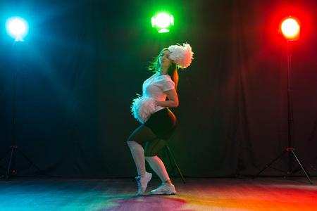 Cheerleading happy girl dancing on dark background