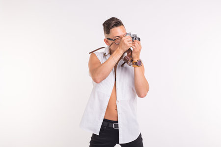 Technologies, photographing and people concept - handsome young man with retro camera over white background Foto de archivo