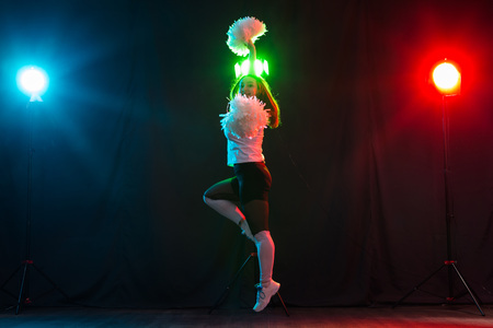 Dancing, sport, beautiful and people concept - young cheerleader girl in darkness show pom poms and smile