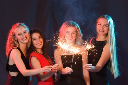New year party, celebration and holidays concept - group of friends having fun with sparklers Stock Photo
