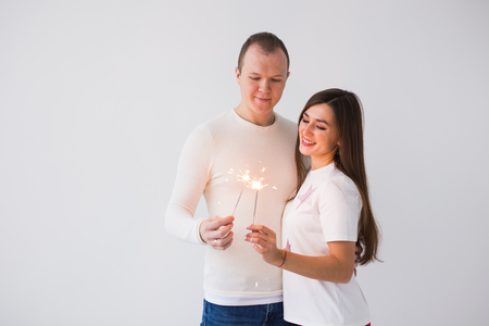 Romantic beautiful couple having date at Valentines Day. Man and woman holding sparklers on white background with copy space
