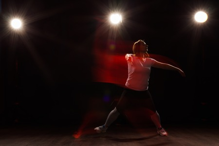 Dancing, sport, beautiful and people concept - young woman dancing in darkness jumped in colourful light