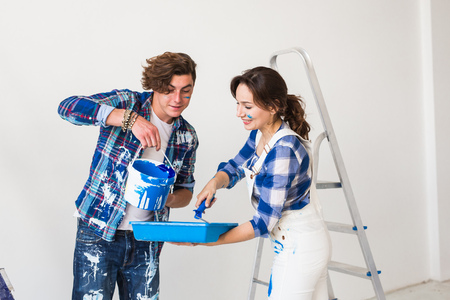 People, repair and renovation concept - Beautiful woman and handsome man paints the wall in new apartment