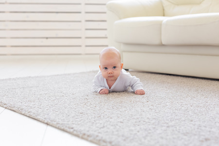 Childhood, babyhood and people concept - little baby boy or girl crawling on floor at home and looking at you