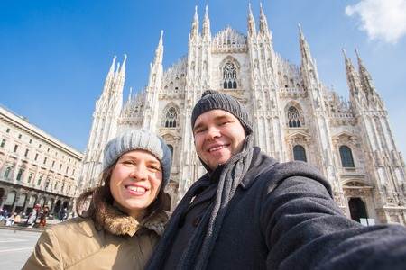 Couple taking self portrait in Duomo square in Milan. Winter holidays, traveling and relationship concept 版權商用圖片