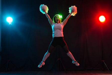 Cheerleading happy girl dancing on dark background