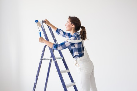 Repair, renovation, new home and people concept - Beautiful woman standing on the ladder during redecoration Standard-Bild - 112020582