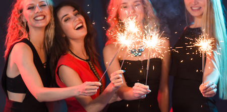Celebrating with fun. Group of cheerful young women carrying sparklers. New year, holidays and party concept.