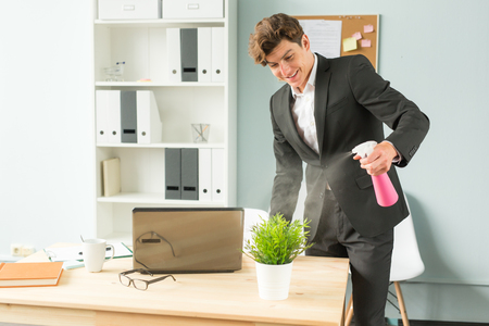 Business people, fun and potted plants concept - young funny businessman watering plant at office Imagens