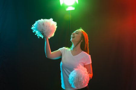 Cheerleading young woman dancing with pom-poms on colourful background