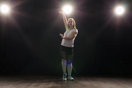 Young beautiful slim woman dancing jazz-funk on a black studio background