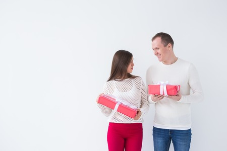 People, christmas, birthday, holidays and valentines day concept - happy young man and woman with gift boxes on white background with copy space Banco de Imagens