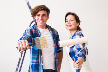 Renovation, redecoration and people concept - young family doing repair and smiling