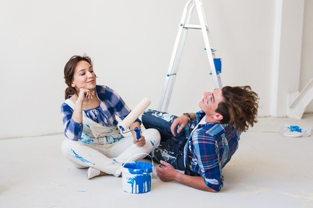 People, repair and relationship concept - Young funny couple doing renovation in new apartment Reklamní fotografie