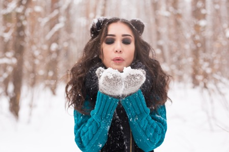 Christmas, holidays and season concept - Young happy brunette woman blowing snow in the winter nature