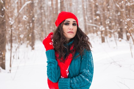 Winter, season and people concept - Young pretty woman walking in snowy park Reklamní fotografie