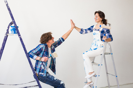 Teamwork, renovation and repair concept - Young man and attractive woman covered in paint sitting on ladders
