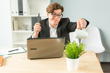 Office, humor, joke and business people concept - handsome man working in office, watering potted plant, sitting with spoon in his hands and smiling